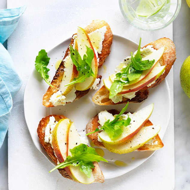 Toasted French baguette slices with ricotta, pear and rocket